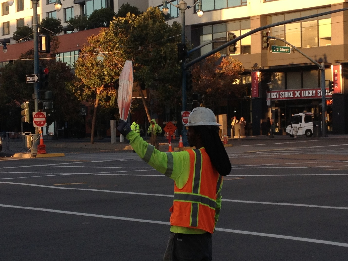 A woman in a safety vest and hard hat holds up a stop sign in the middle of the 4th and King intersection.