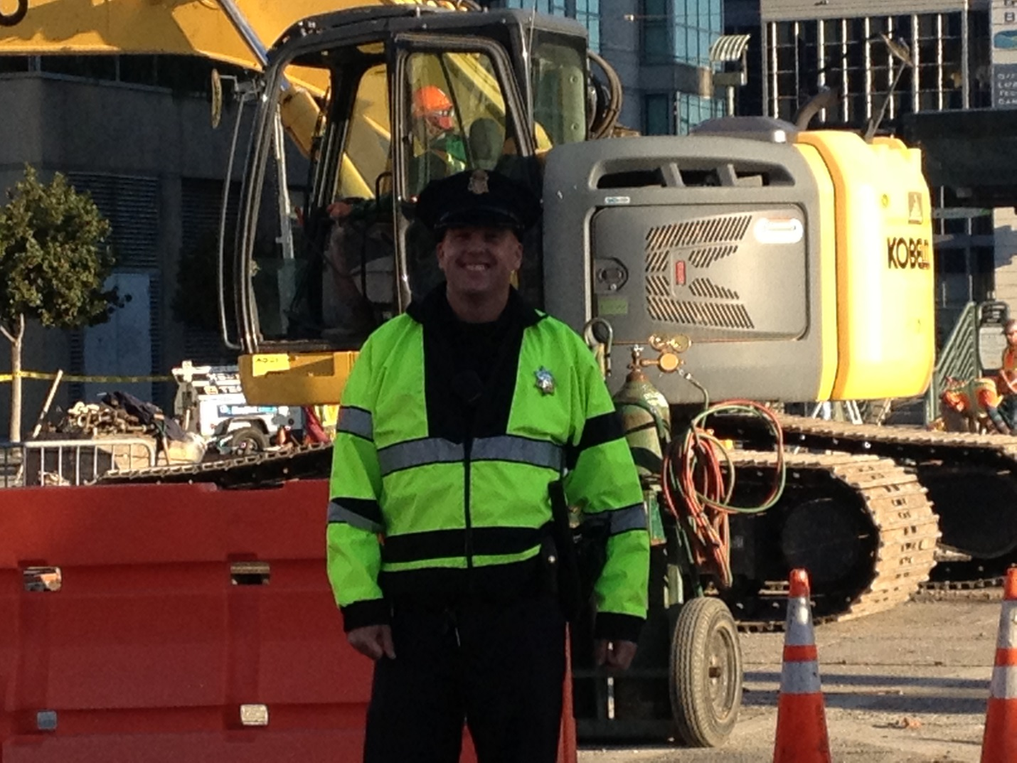 A police officer wearing a reflective safety jacket stands in front of construction equipment.