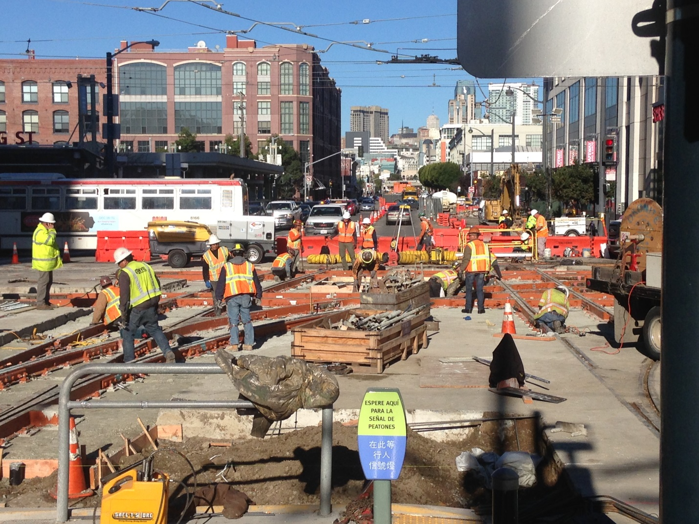 High-angle photograph of the 4th and King construction site with crews in safety vests and hard hats with a Muni bus and other traffic in the background.