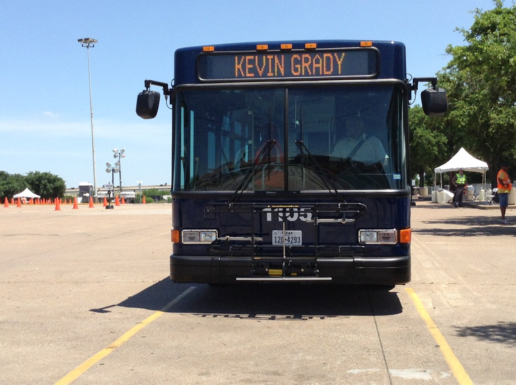 "Head sign on a dark blue bus reads ""Kevin Grady"" as the bus sits in a large, empty parking lot."