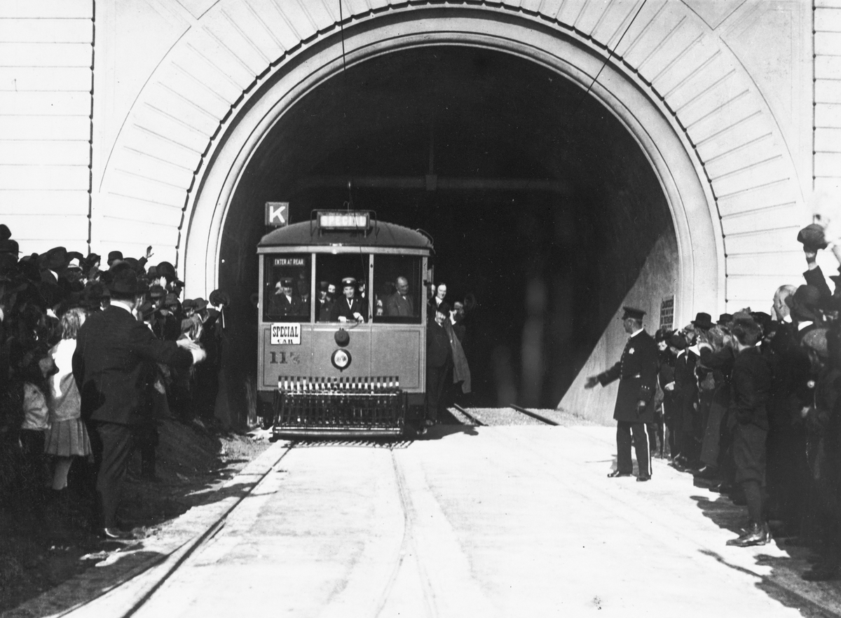 1918 photograph of Mayor Rolph and dignitaries on a K Line streetcar at the openin gof the Twin Peaks Tunnel flanked by crowds.