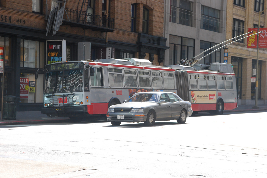 Muni trolley bus on the 14 Mission route sits at the curb on Mission Street in downtown SF.