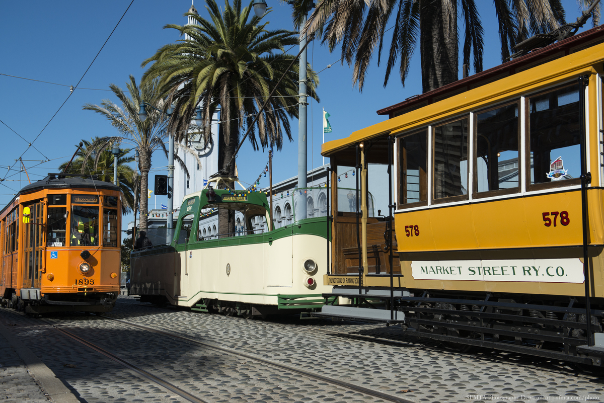 Colorful historic streetcars in yellow, green and orange, sit on The Embarcadero with a blue sky overhead.