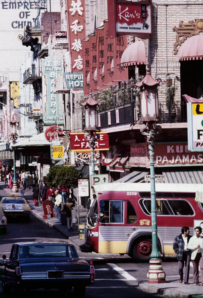Colorful street scene of Chinatown in 1972 with a maroon and yellow Muni bus crossing the street.