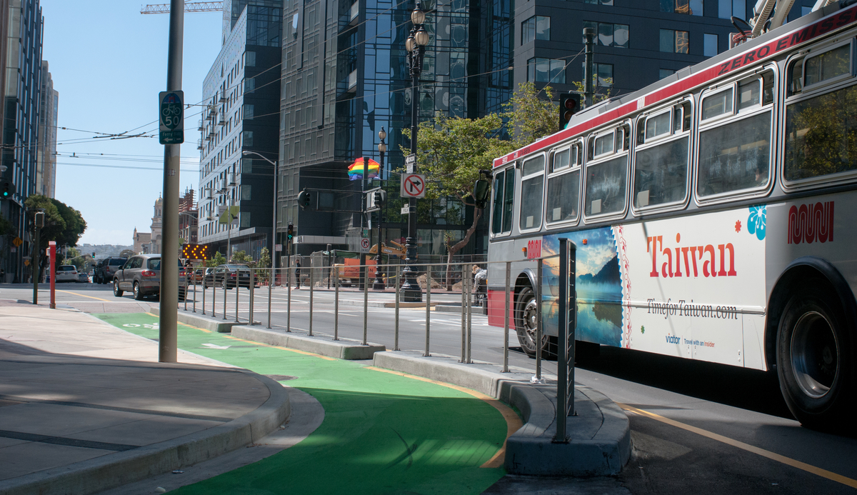 Muni bus travels south on Polk Street with the green painted Polk St. contraflow bike lane in the foreground.