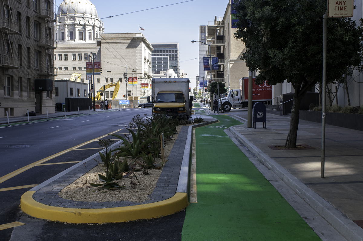 The Polk Street contraflow bike lane with green paint and landscaping, facing north on Polk St. with City Hall in the background