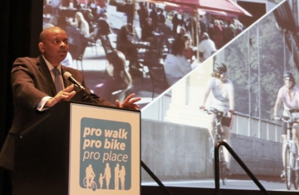 "Transportation Secretary Foxx stands at a lecturn labeled ""Pro Walk, Pro Bike, Pro Place."" Photographs of bicyclissts and people at a cafe are projected behind him."