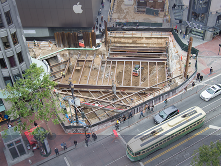 Aerial photograph of the subterranean construction site at Market, Stockton and Ellis streets with a streetcar, autos and pedestrisans passing by.