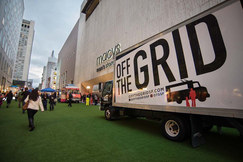 "A truck sits on an astroturf-lined street next to Macy's Men's Store with ""Off the Grid"" in bold black text on the side."