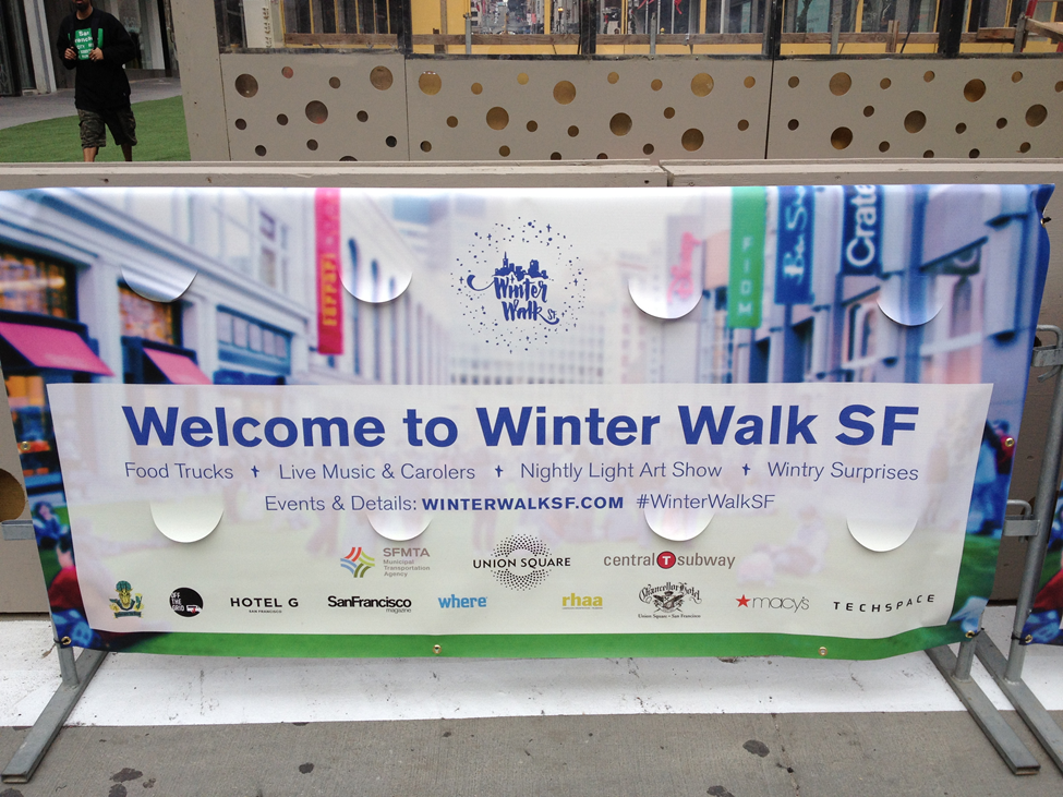 "Event sign on the street, ""Welcome to Winter Walk SF"" with sponsor logos and website, ""winterwalksf.com"" and hashtag ""#WinterWalkSF"""