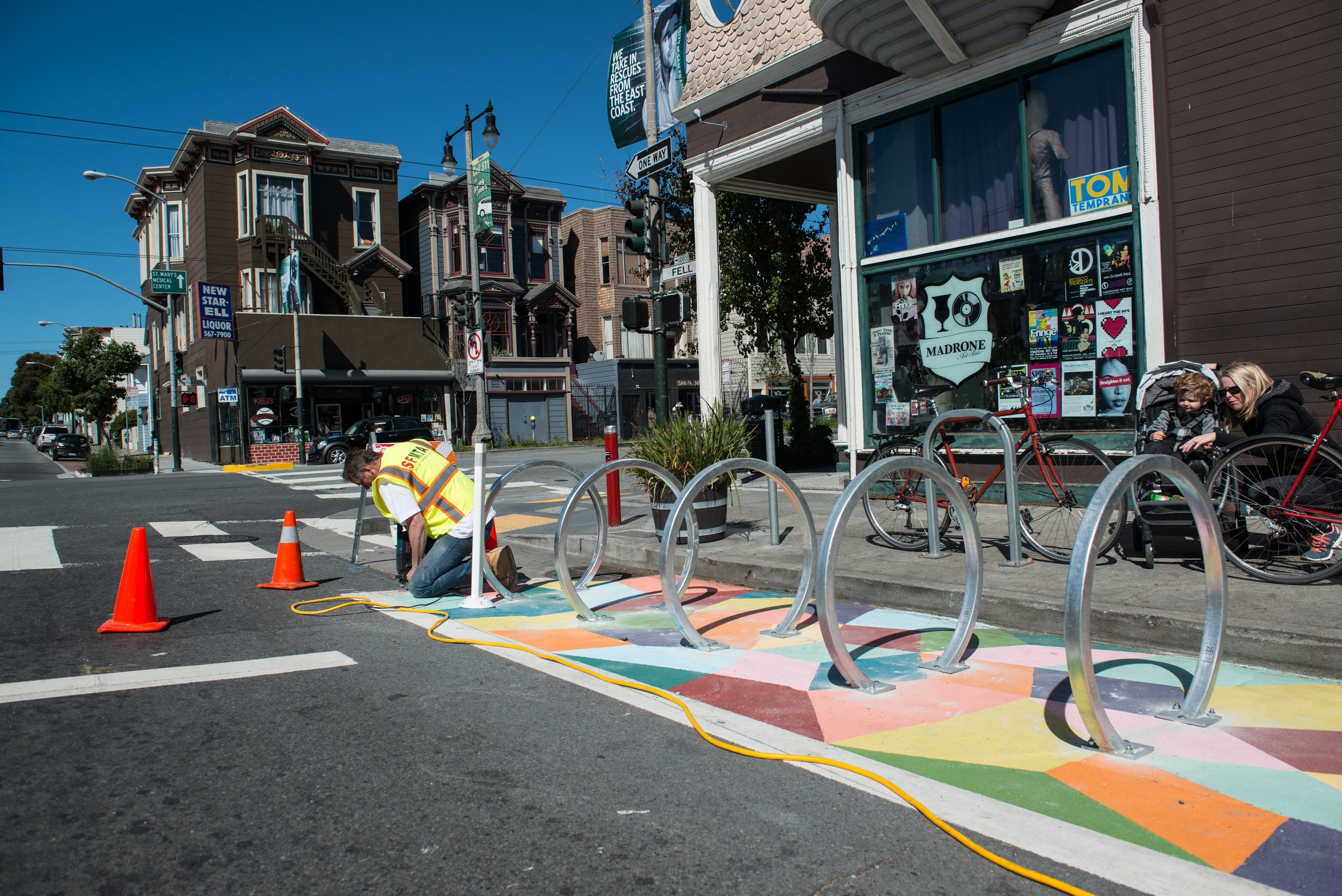 MTA worker installing new circular bike rack above newly painted geometric street mural during the day