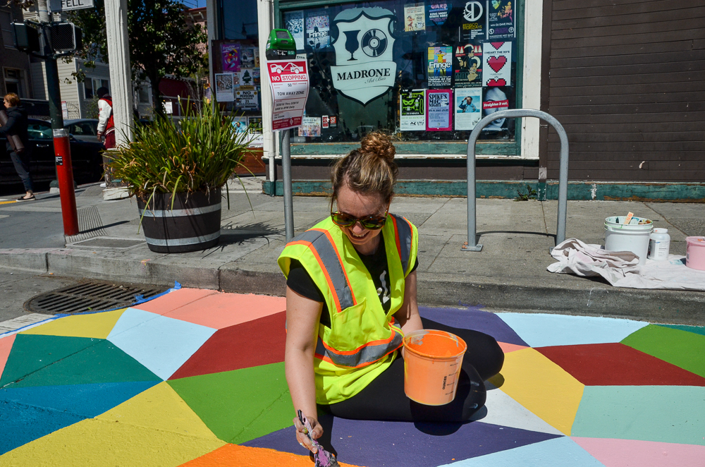 Business owner sitting on ground painting new geometric street mural for new bike racks during the day.
