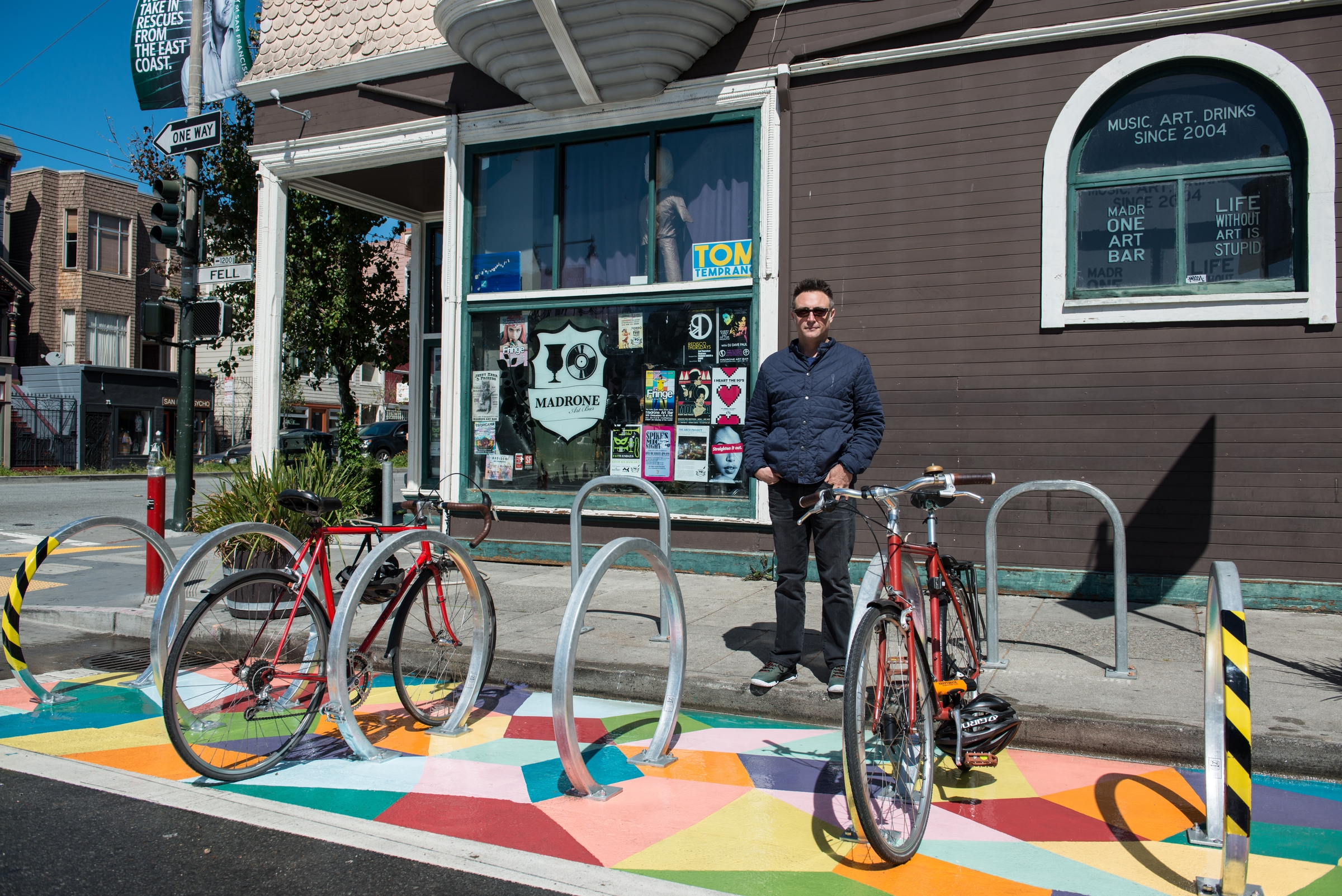Business owner standing on sidewalk in front of newly installed mural and bike racks during the day