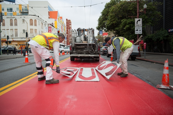 Crew members lay letter stencils to mark a red transit-only lane on Mission Street.