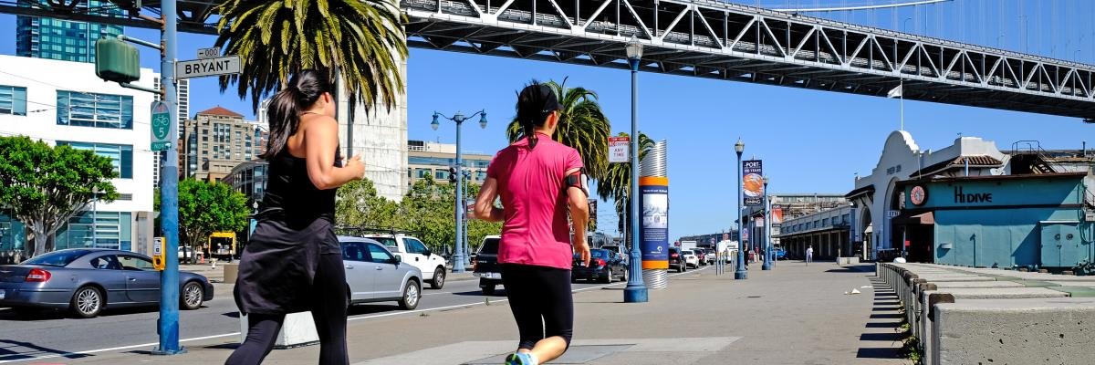 Joggers and pedestrians on the Embarcadero pass under the Bay Bridge on a sunny day in 2014