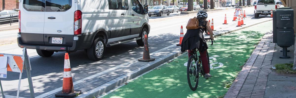 Photo of woman biking on new green bikeway under construction