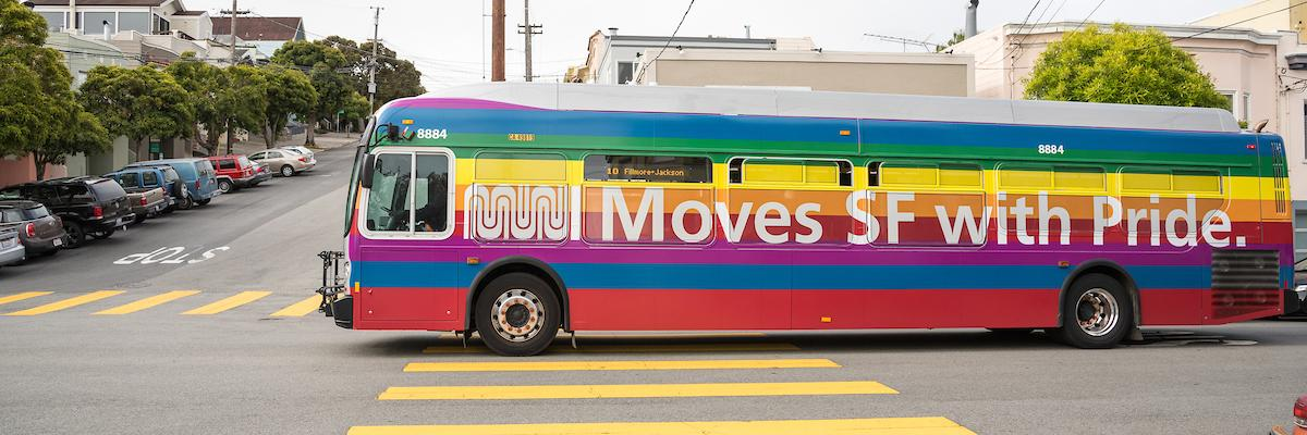 "Muni bus wrapped in rainbow flag with words ""Muni Moves SF with Pride"""