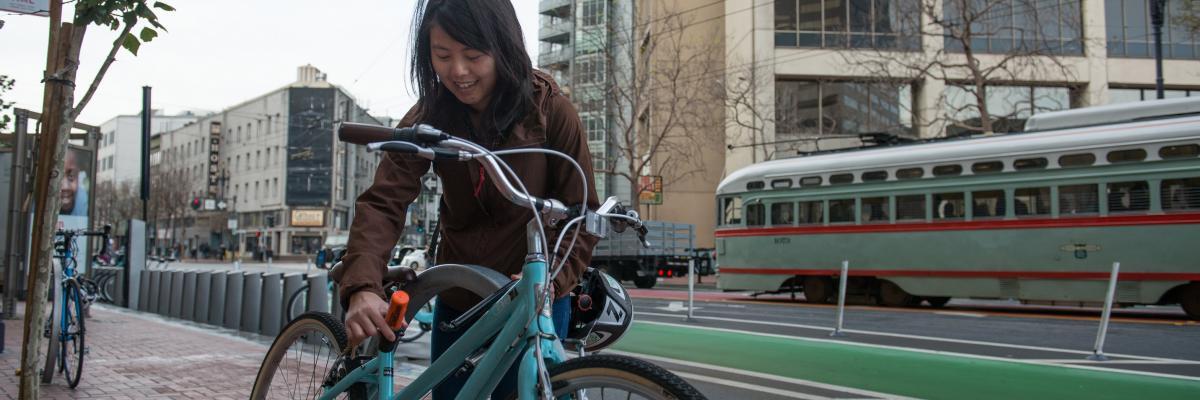 Woman locks her bike to a rack on market street
