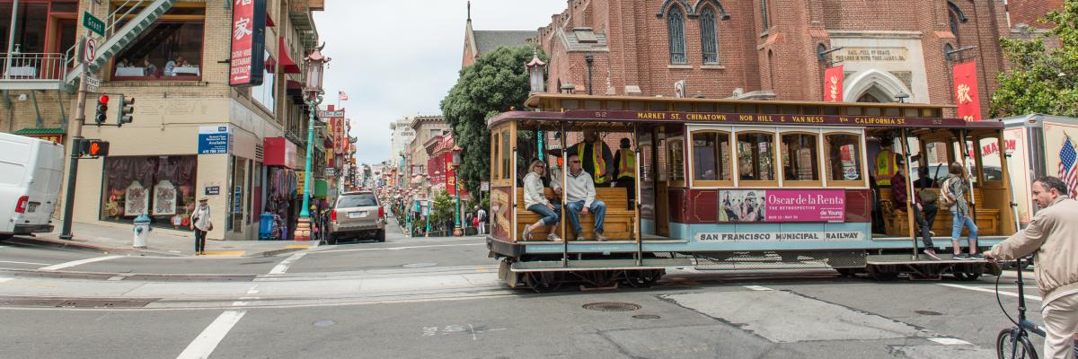 a couple rides a cable car through chinatown