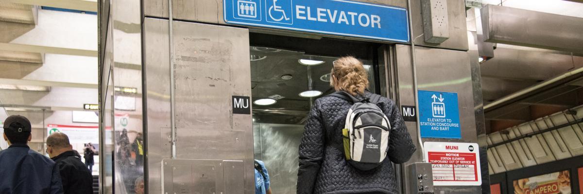 Woman enters an elevator at a Muni Metro station