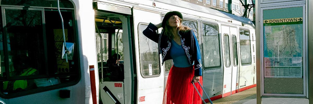 A woman strikes a dance pose outside of the Muni train car.