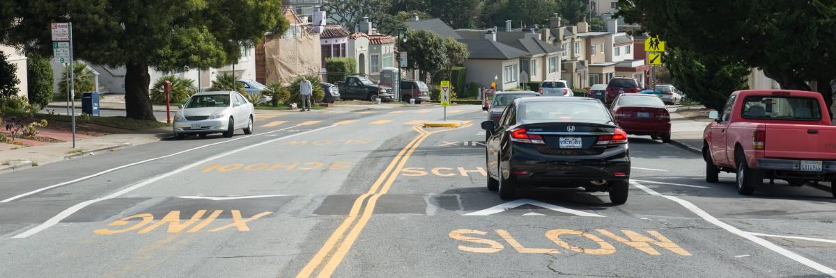 View of a school safety zone with car driving over a speed hump