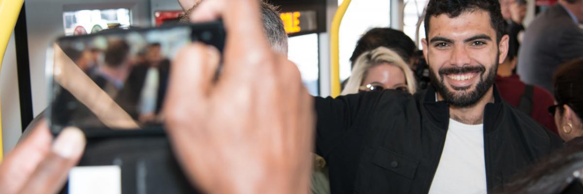 Man on Muni bus gets his picture taken.