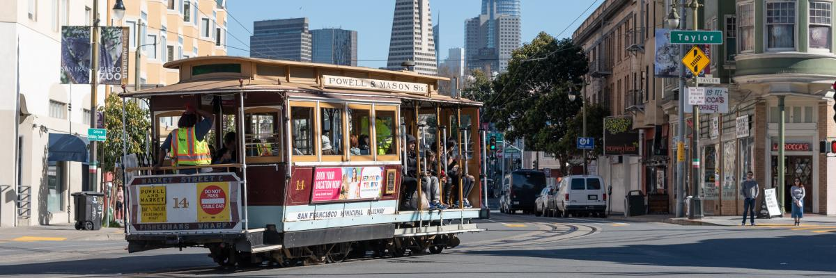 A cable car rounds a corner with the downtown skyline in the background