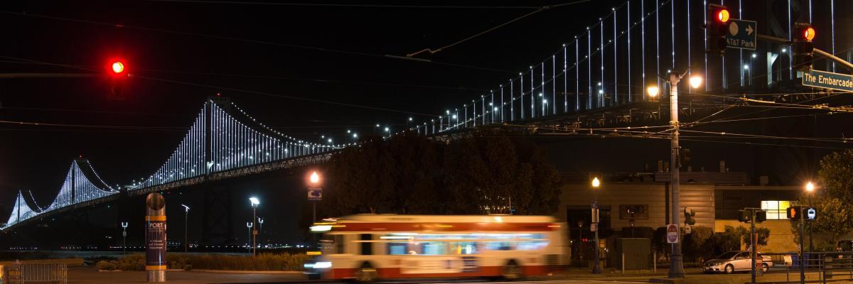 Late night Muni bus seen on the streets, below the Bay Bridge.