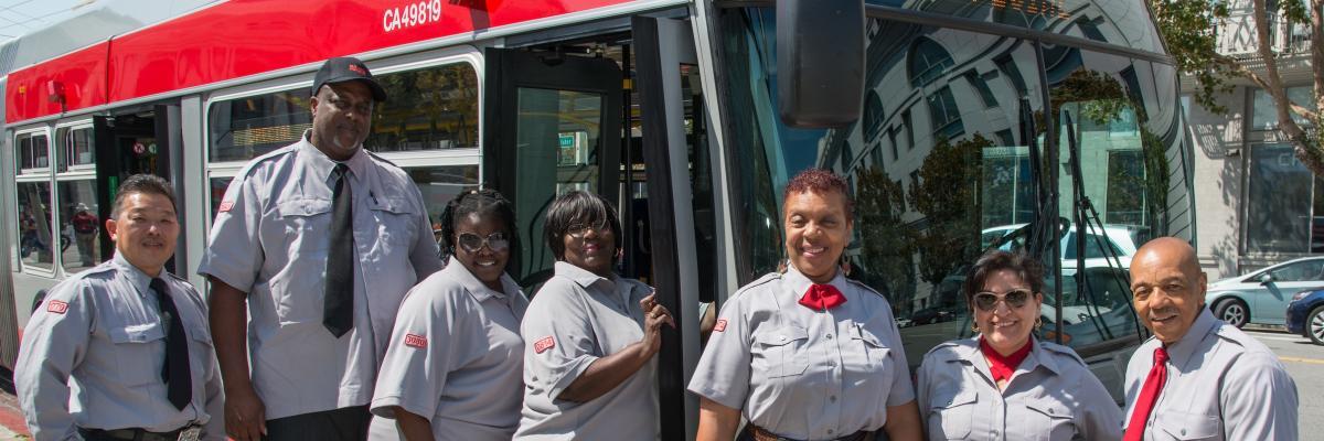 Muni operators stand alongside a Muni bus