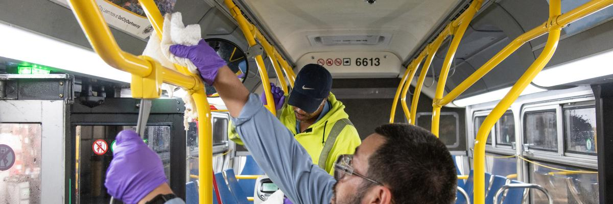 Image of car cleaning staff wiping down the interior of a bus