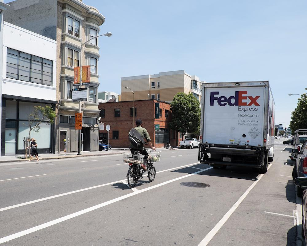 8th Street before: a bicyclist is traveling in the bike lane. a delivery truck is parked in the bike lane ahead.