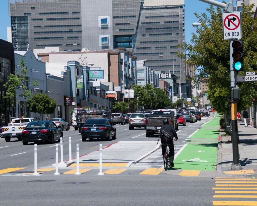7th Street after: transit boarding island and a bicyclist riding in a protected bikeway with green paint.