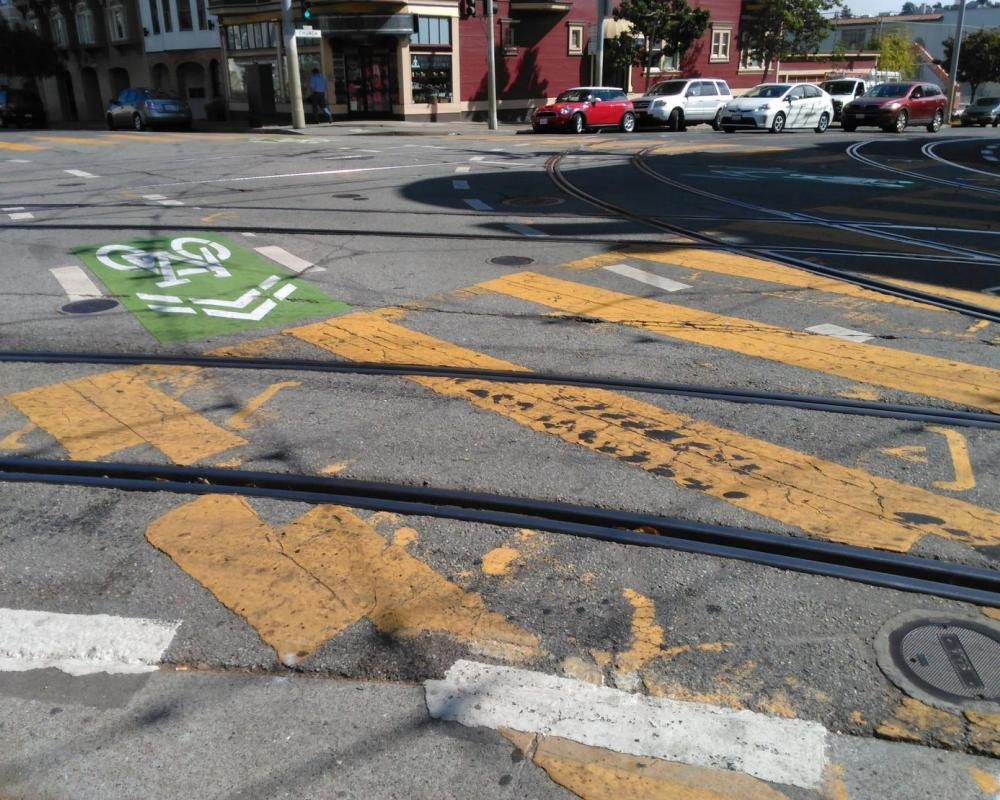 Green-backed sharrows, yellow continental crosswalks, and other roadway markings are overlaid with tracks in the roadway