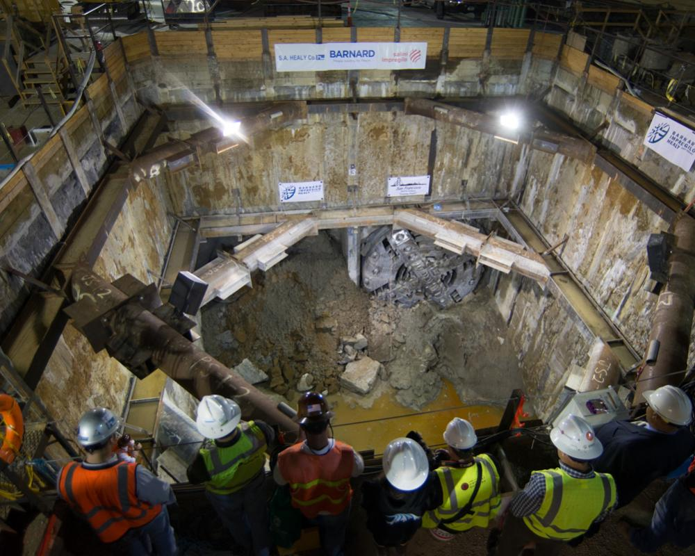 Project and agency staff watch TBM Big Alma emerge inside the North Beach retrieval shaft in 2014.