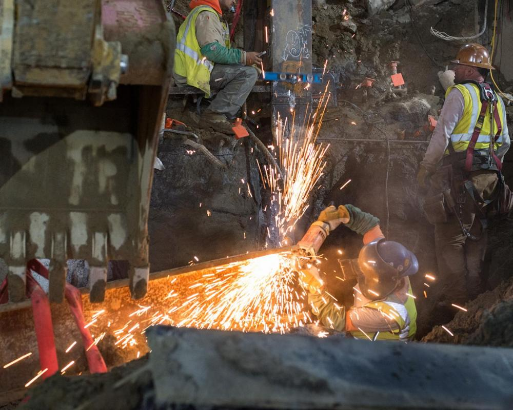A metalworker cleans up the ends of a large steel I-beam for welding, which will be used as a bracket at the south headwall.
