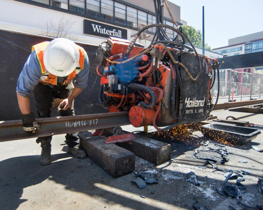 Two short sections of rail are welded together using this machine near 4th and Bluxome.