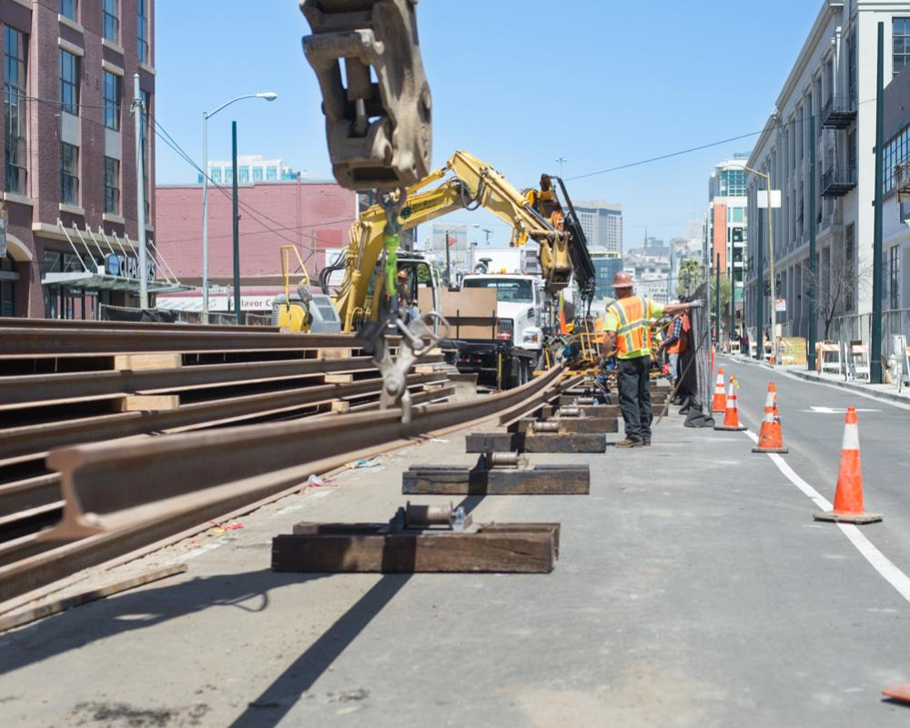 Another length of rail is lifted into place onto steel rollers to be moved north up 4th Street.