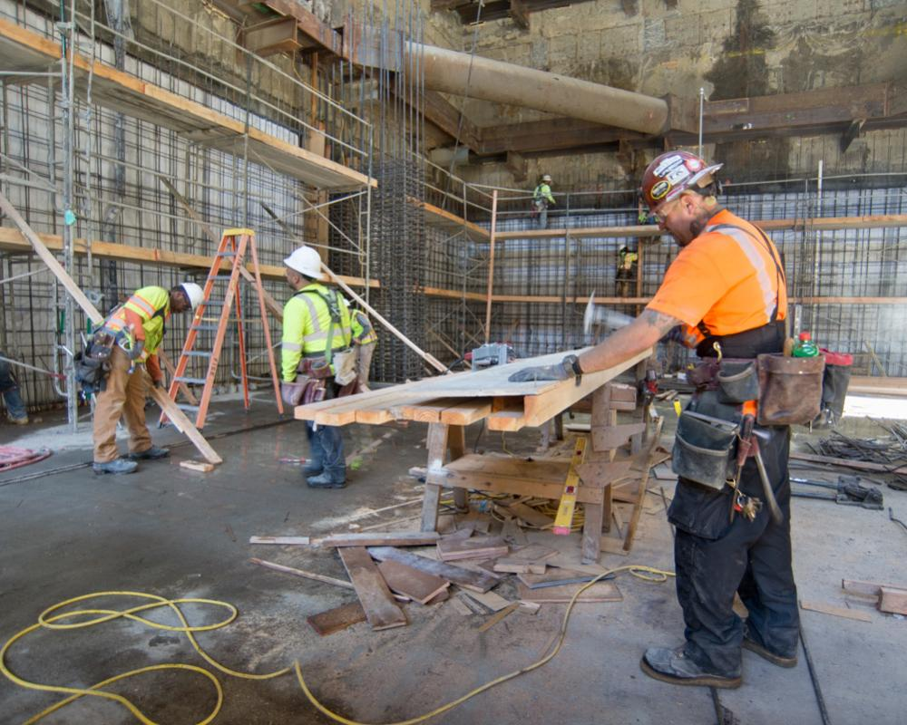 A carpenter builds part of a concrete form in the northwest corner of the YBM station headhouse.