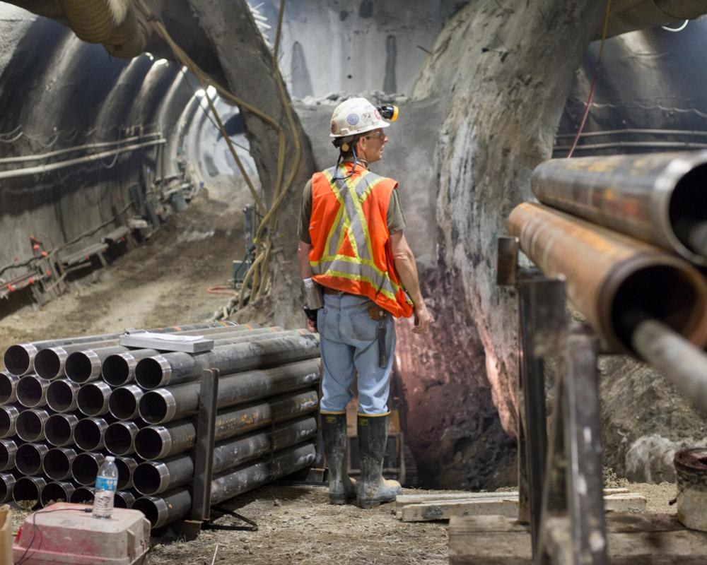 Drill casings surround a worker pausing for a bulldozer to pass during excavation of the Chinatown Station platform cavern.