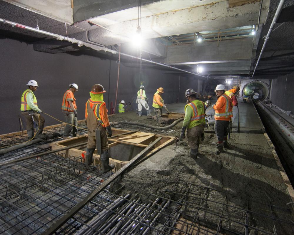 A crew pours concrete around future elevator footings inside the Yerba Buena/Moscone station box.