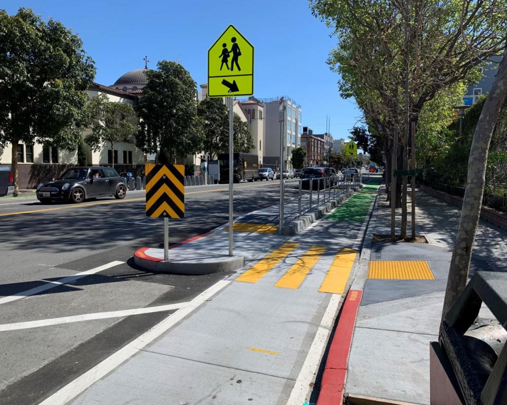 New protected bikeway, including a school loading island on Valencia