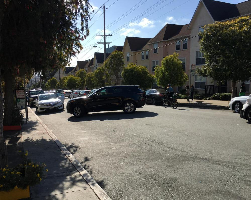 View of queued vehicles on Page Street between Webster and Buchanan streets, with an SUV making a mid-block maneuver.