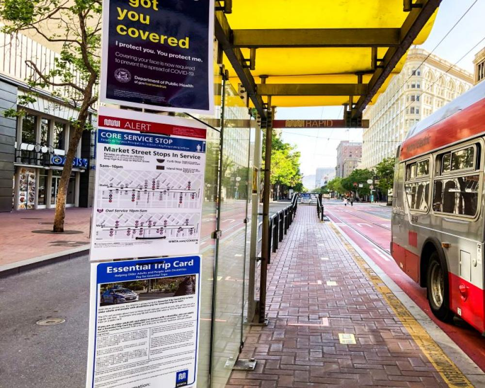 Photo of face mask, wayfinding and ETC signs at a boarding island on Market Street.