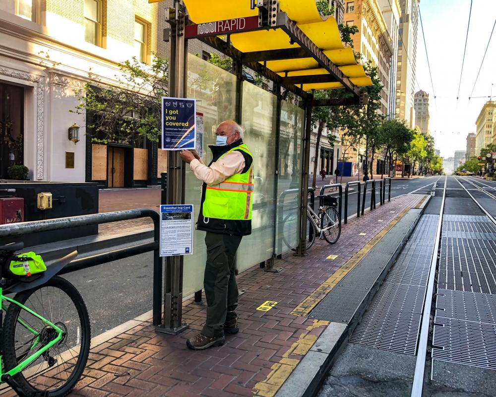 Photo of a Market Street Ambassador posting new face mask, ETC, and wayfinding signage on a boarding island bus stop.