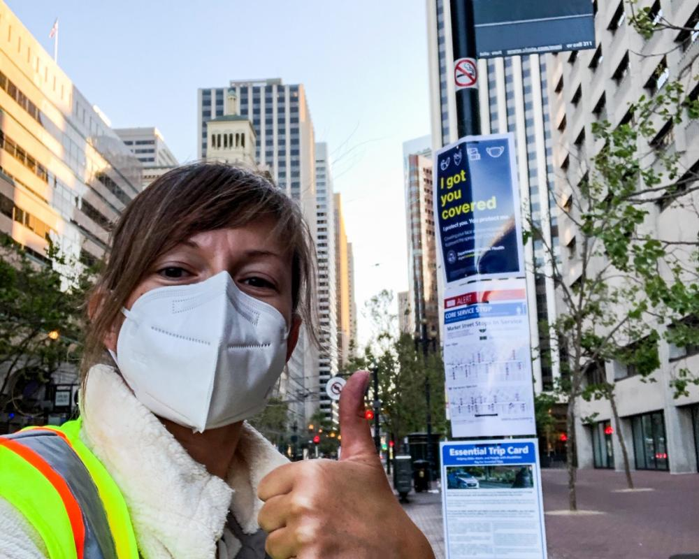 Photo of SFMTA staff giving a thumbs up after posting face mask, wayfinding, and ETC signs at a bus stop on Market Street.