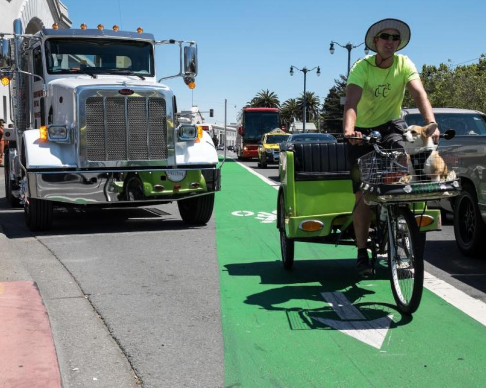 View of a pedicab driver riding in the northbound bike lane on The Embarcadero in front of Pier 35, looking south