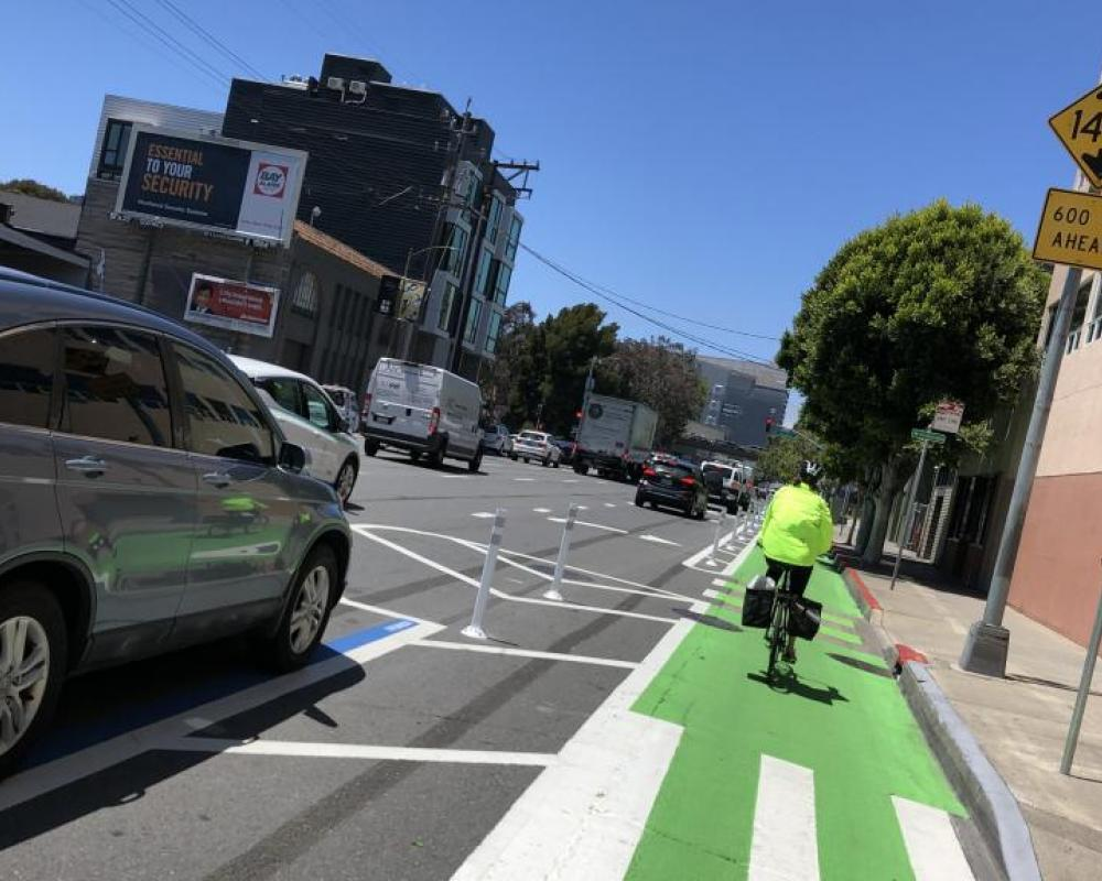 7th Street after: bicyclist riding in a protected bikeway with green paint