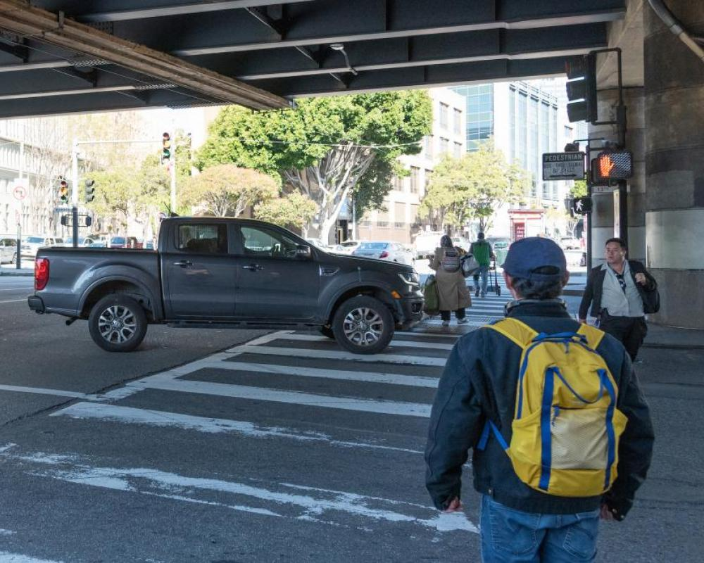 pedestrians walking in the crosswalk at 13th Street and Mission Street and a turning pick-up truck