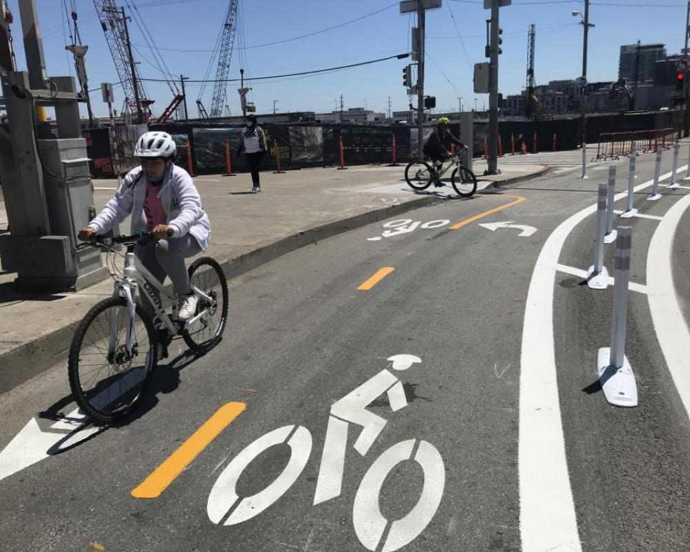 two people riding in a two-way protected bikeway that is marked by bicycle symbols on the roadway
